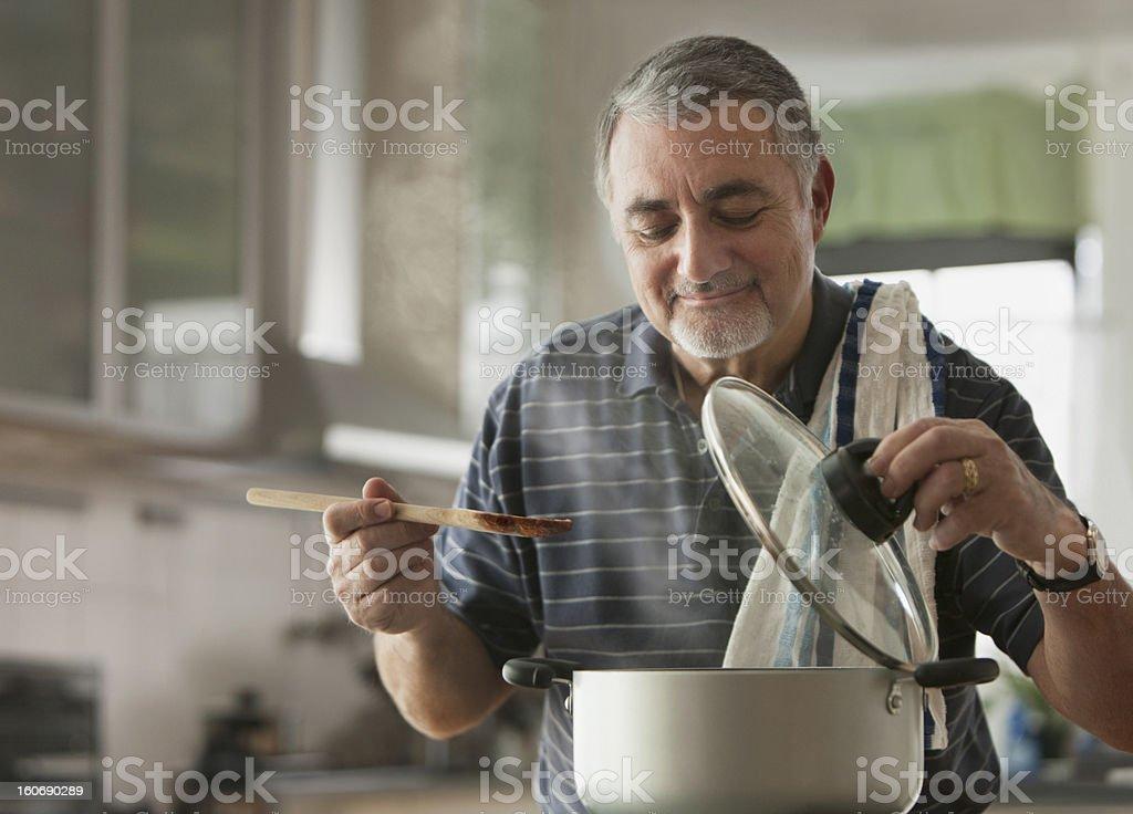 Elderly man cooking stock photo
