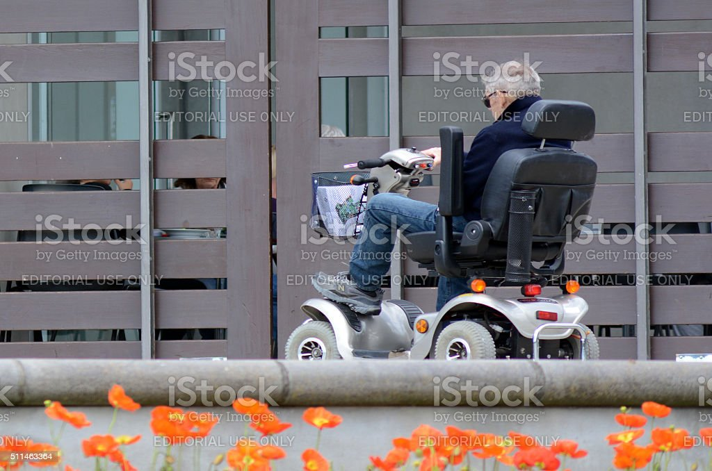 Elderly Man Drives Mobility Scooter stock photo