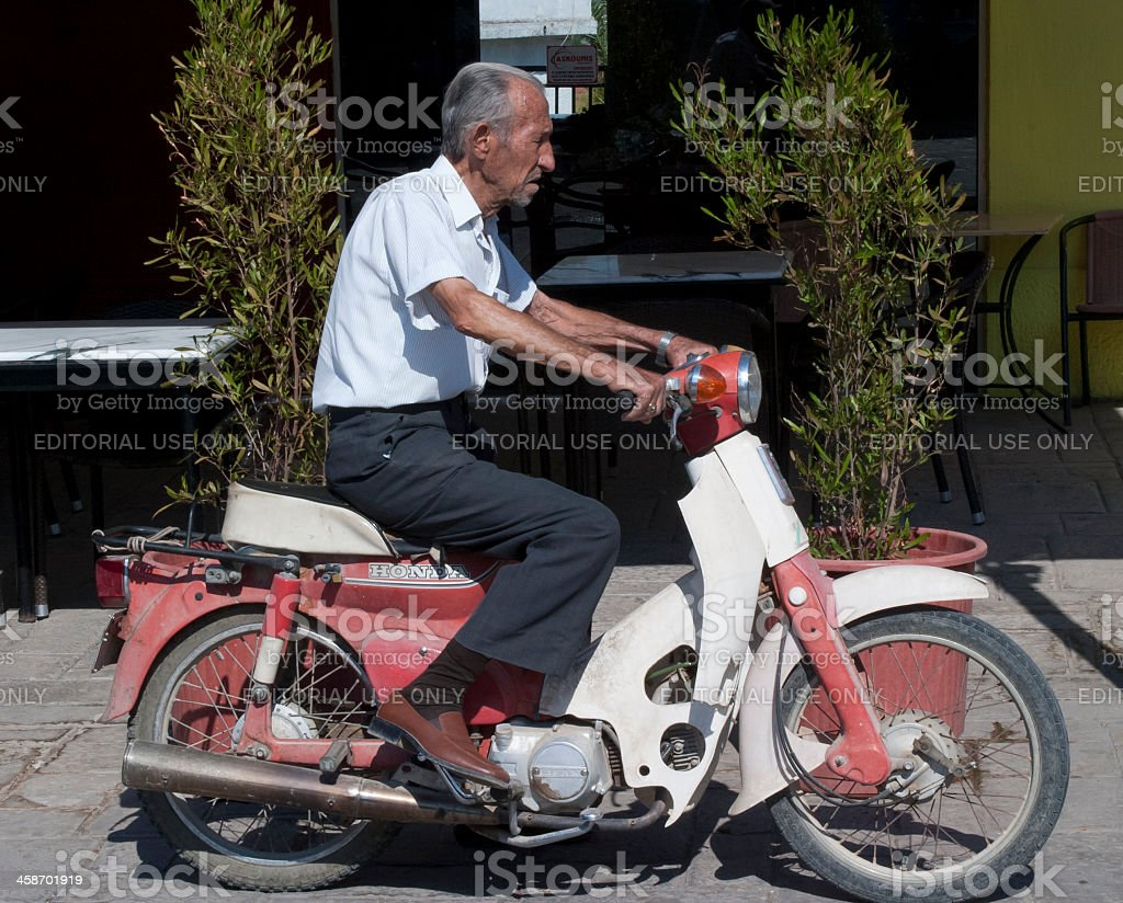 Elderly Man Driving Honda Motorcycle royalty-free stock photo