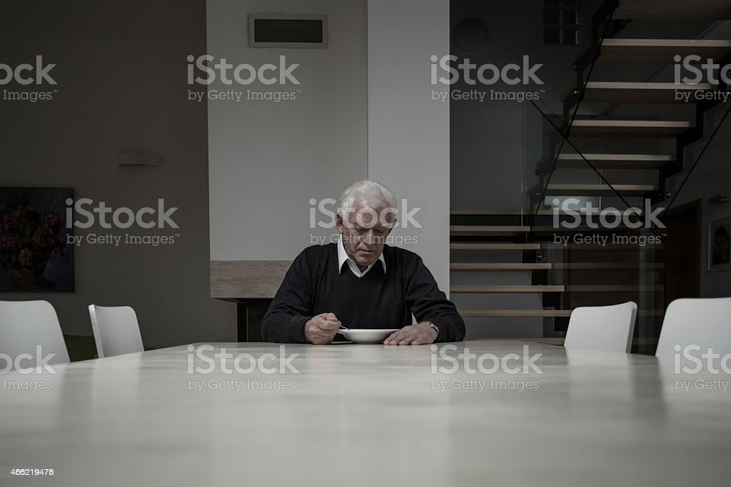 Elderly man eating dinner stock photo
