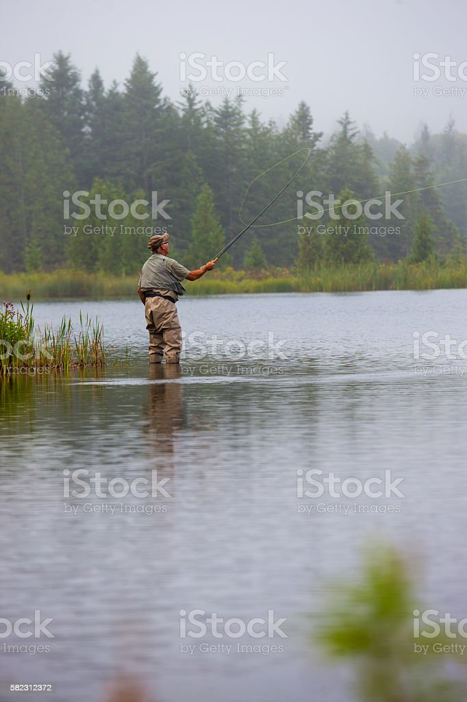 Elderly man flyfishing at sunrise stock photo