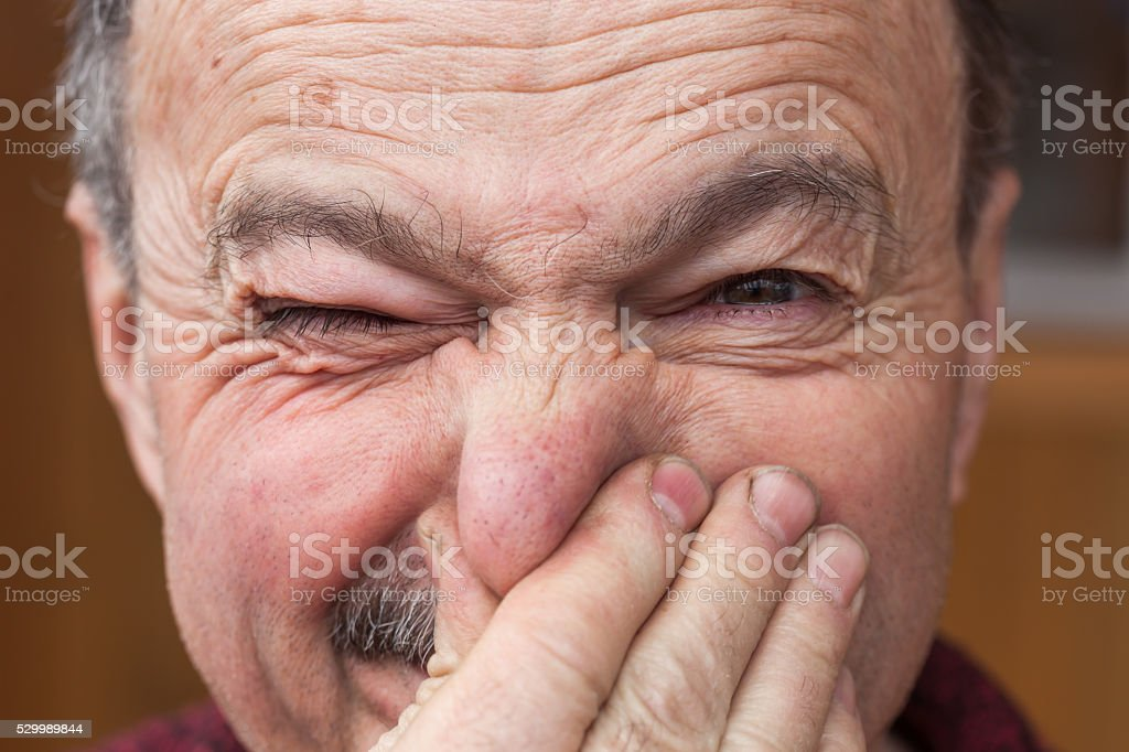 Elderly man hands nose plugs because of unpleasant smell stock photo