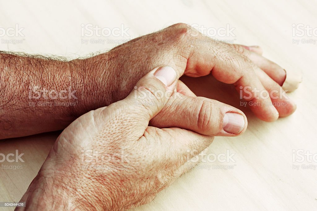elderly man has pain in fingers and hands stock photo
