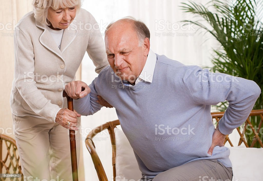 Elderly man having a back pain stock photo