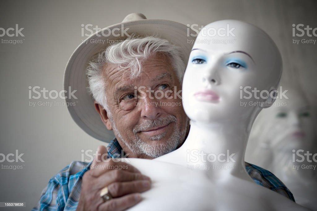 Elderly man holding a mannequin stock photo