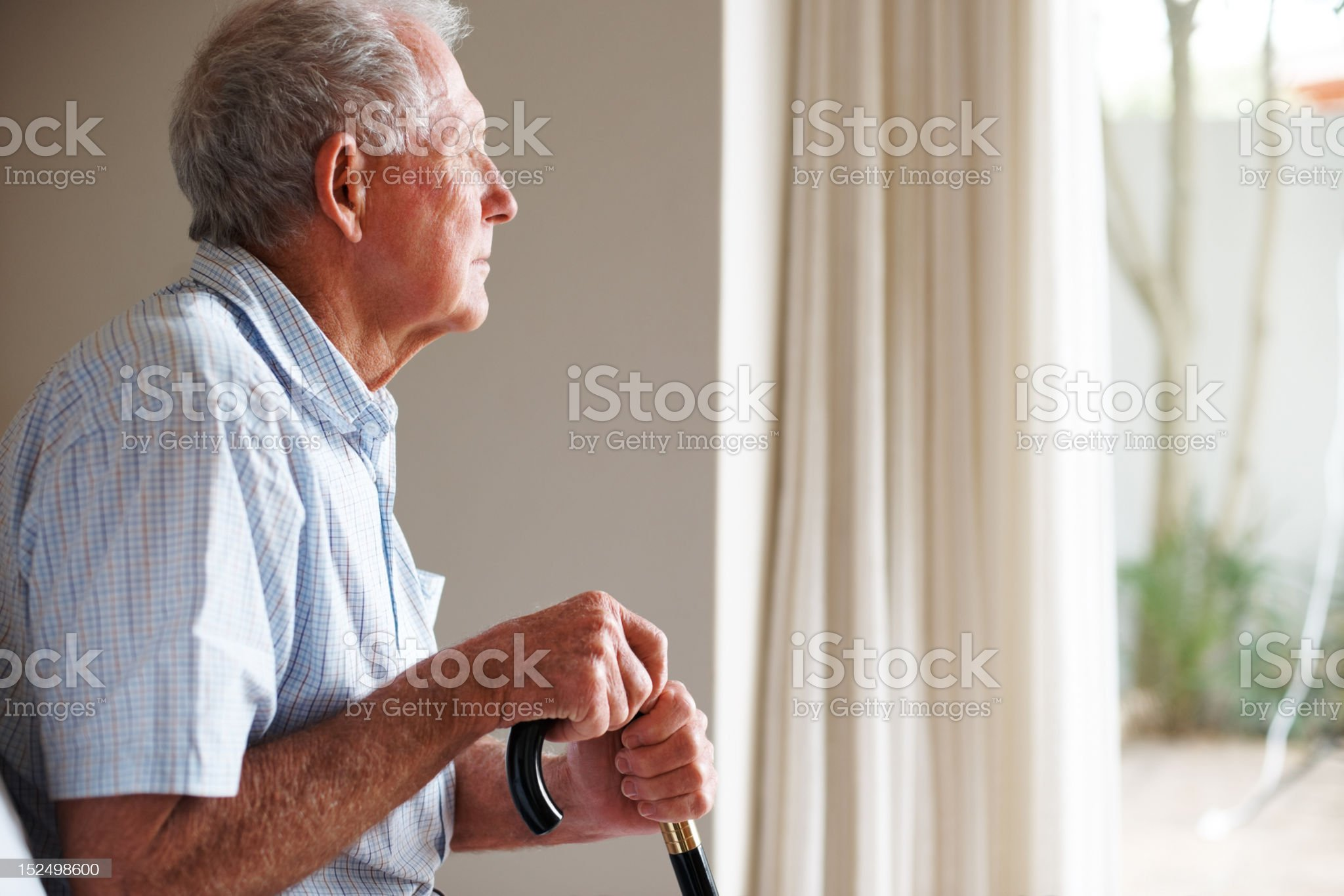 Elderly man holding a walking stick looking outside royalty-free stock photo