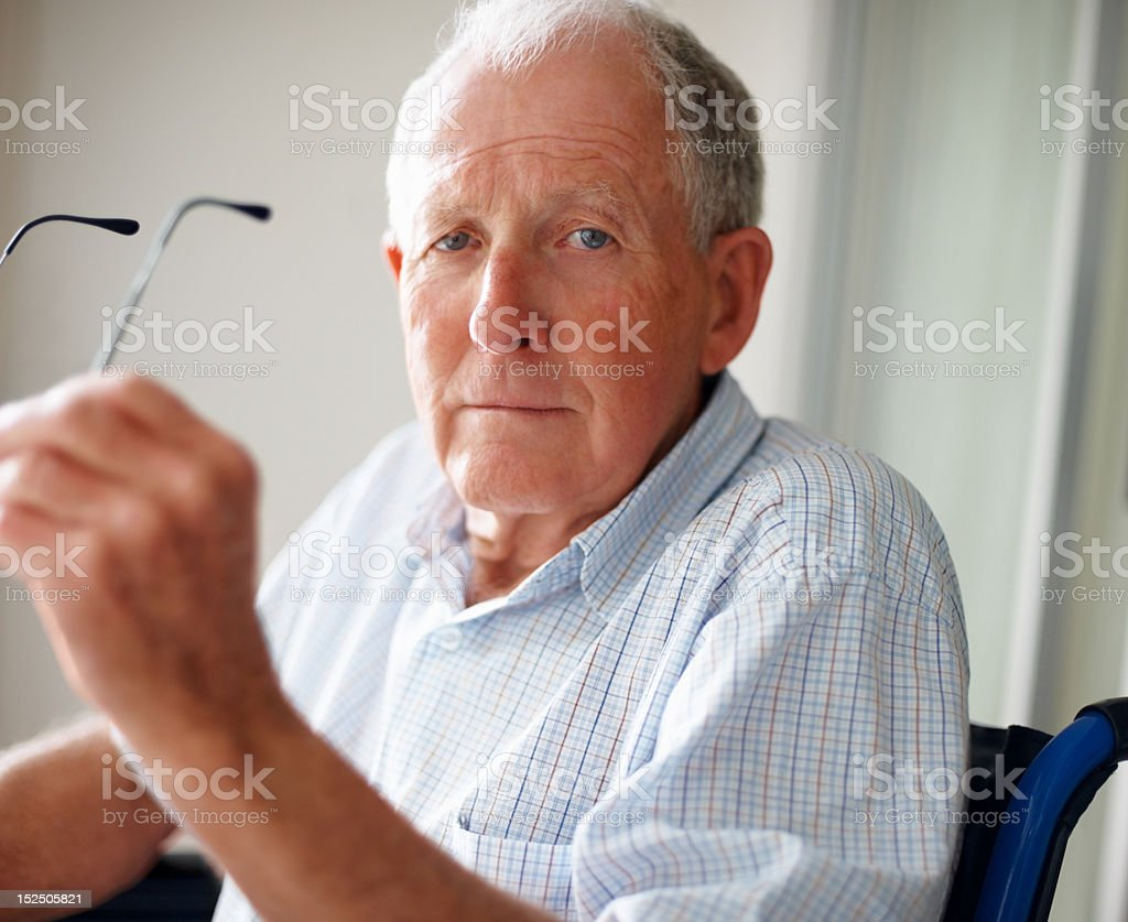 Elderly man holding his glasses royalty-free stock photo