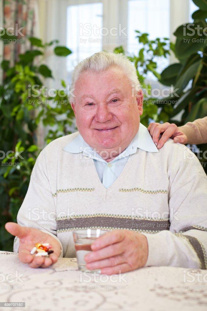 Elderly man holding pills and water stock photo