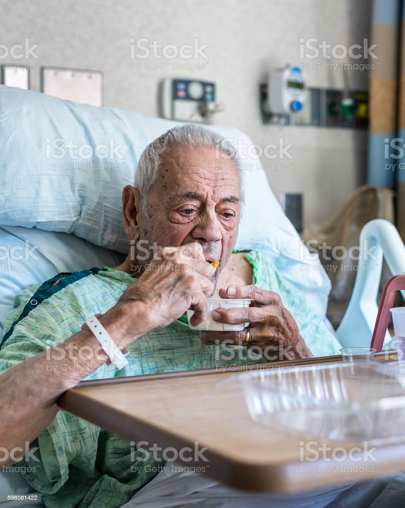 Elderly Man Hospital Bed Patient Eating Breakfast stock photo