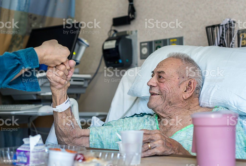 Elderly Man Hospital Patient Fist Bump Greeting Family Member stock photo