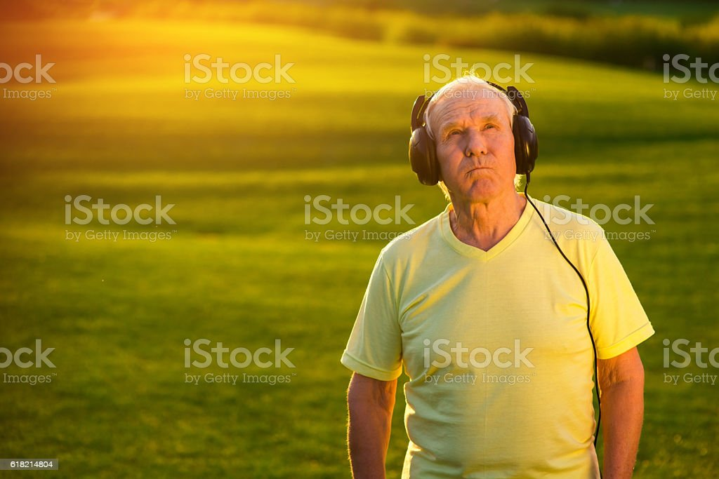 Elderly man in headphones. stock photo