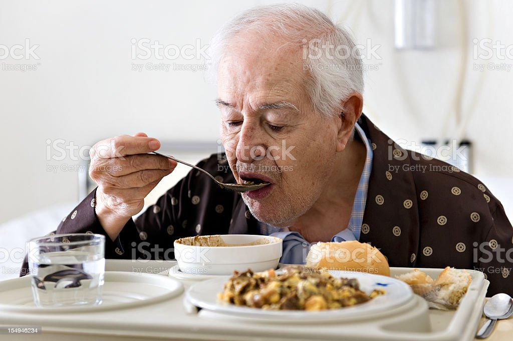 Elderly man in hospital bed eating soup from tray stock photo