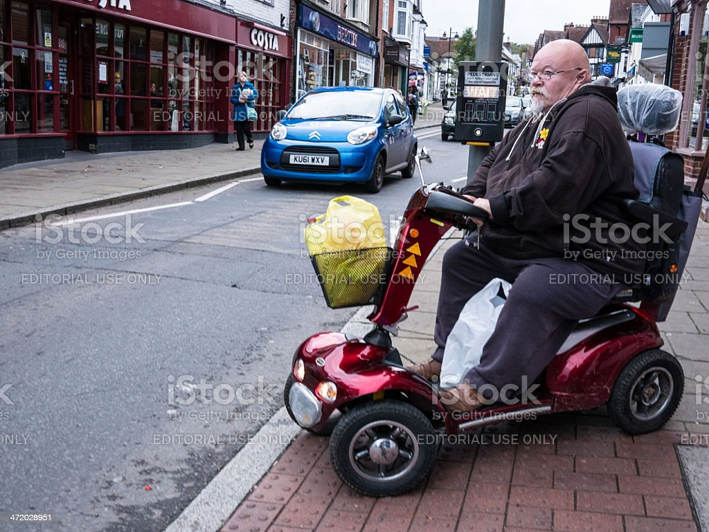 Elderly man in mobility vehicle at pedestrian crossing stock photo