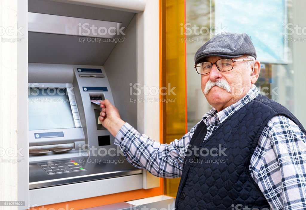 elderly man inserting credit card to ATM stock photo