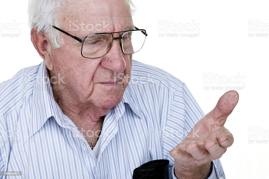 Elderly man looking at his hand royalty-free stock photo
