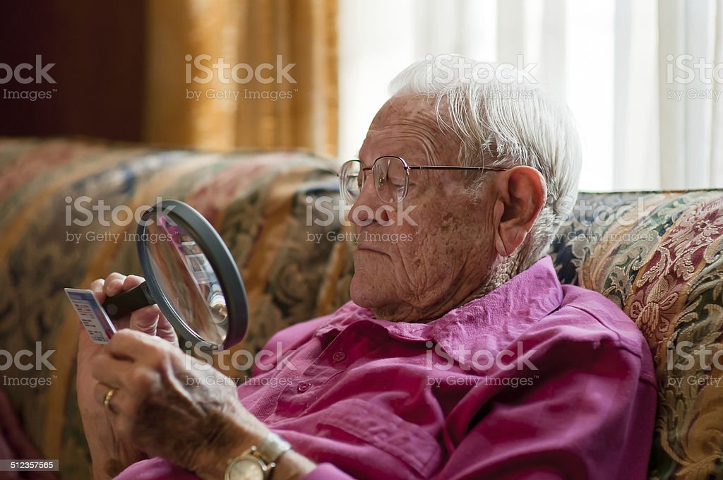 Elderly man looking at object with magnifier stock photo