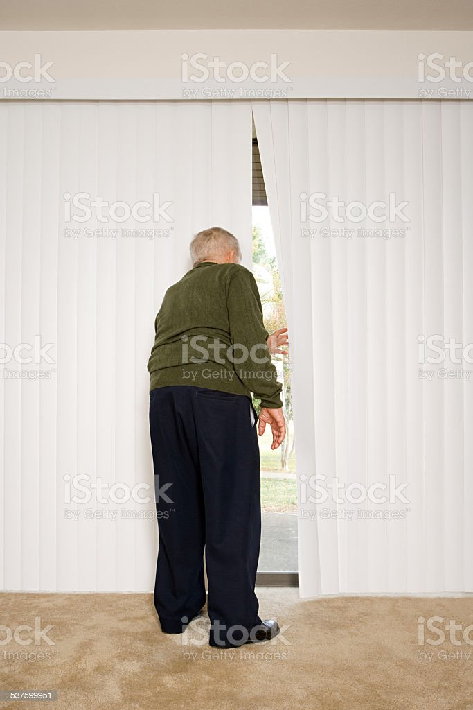 Elderly man looking out of blinds stock photo