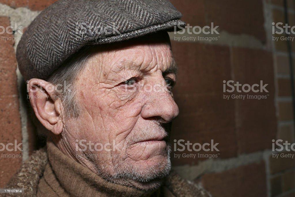 Elderly Man Looking Sad Against a Brick Wall royalty-free stock photo