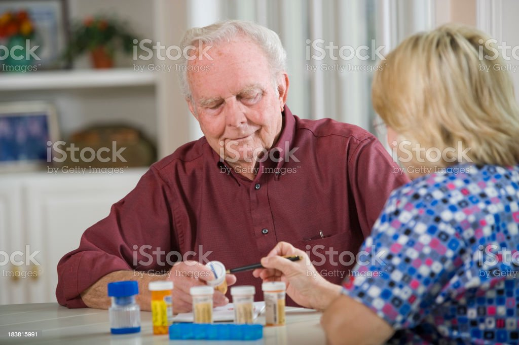 Elderly man, medications, and homecare nurse royalty-free stock photo