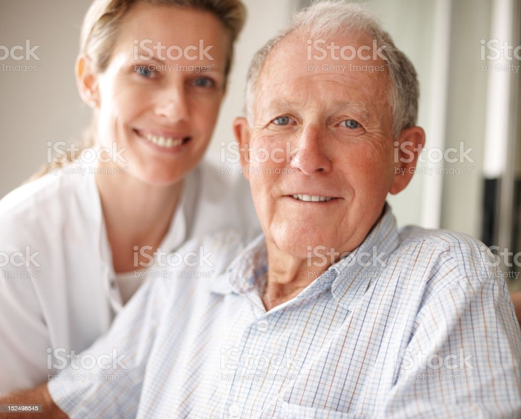 Elderly man on the wheelchair with a nurse royalty-free stock photo