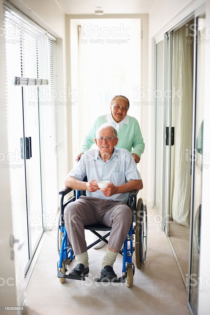Elderly man on wheelchair assisted by his wife royalty-free stock photo