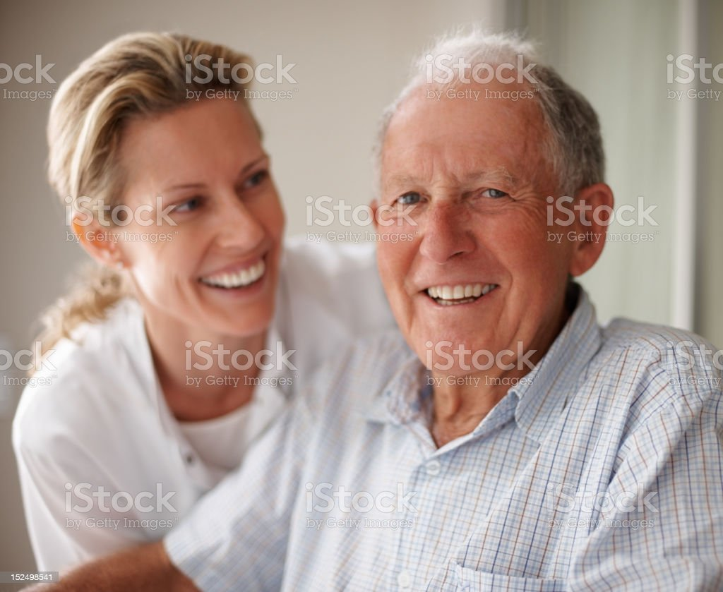 Elderly man on wheelchair with a nurse royalty-free stock photo