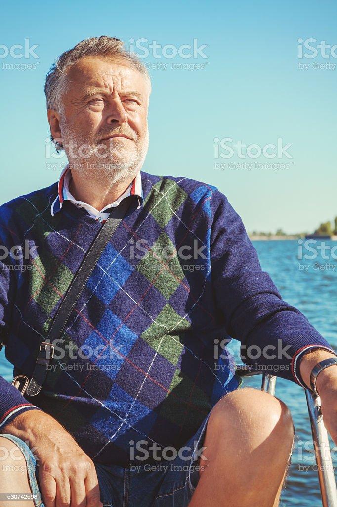 elderly man on yacht at sea stock photo