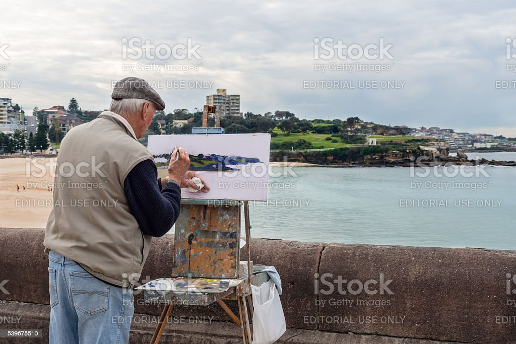 Elderly man painting a landscape stock photo