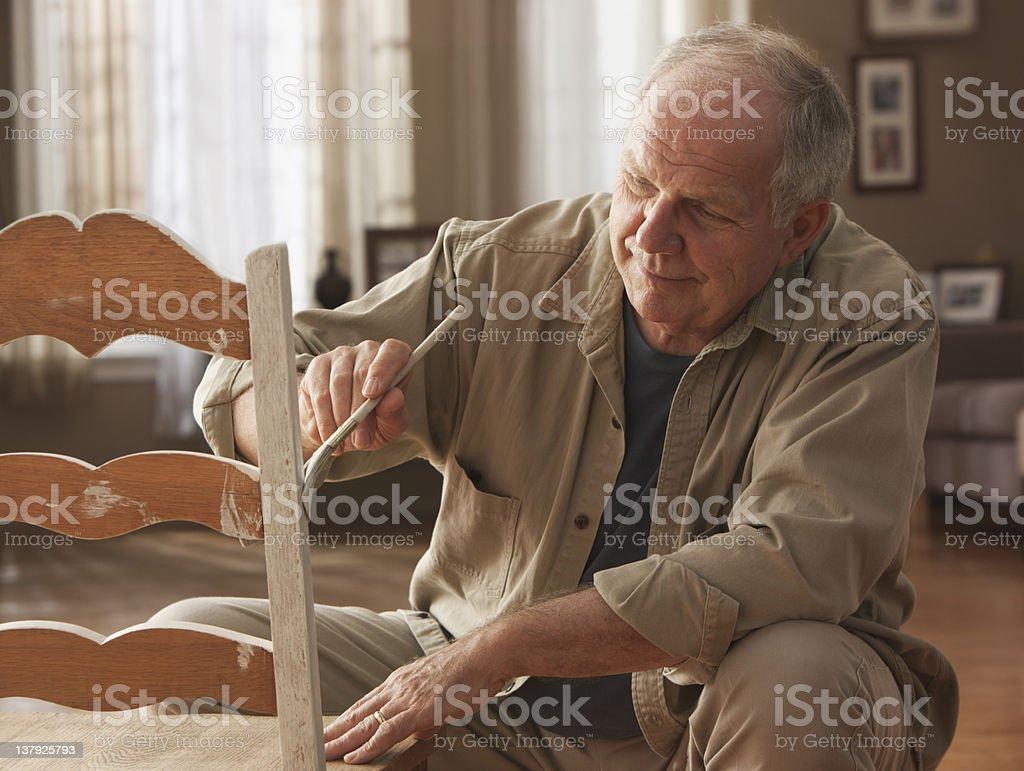 Elderly man painting chair stock photo
