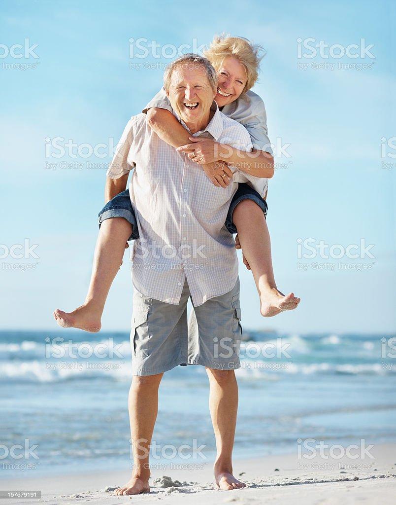 Elderly man piggybacking a woman at the beach royalty-free stock photo