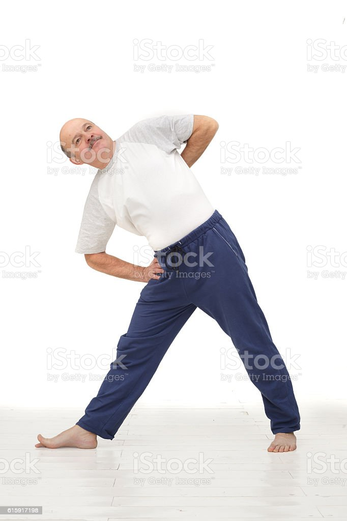 Elderly man practicing yoga or fitness. stock photo