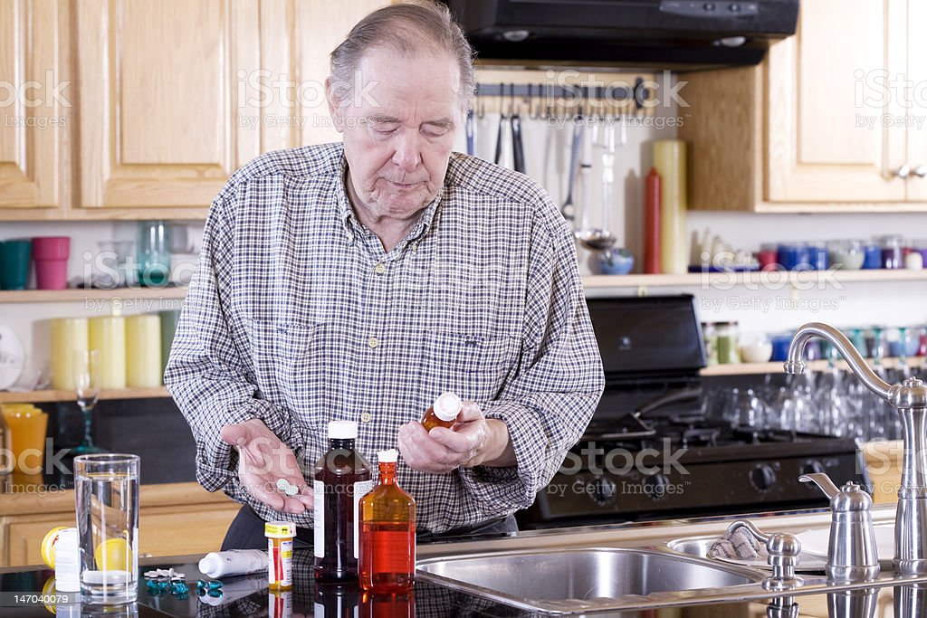 Elderly man preparing to take medicine stock photo