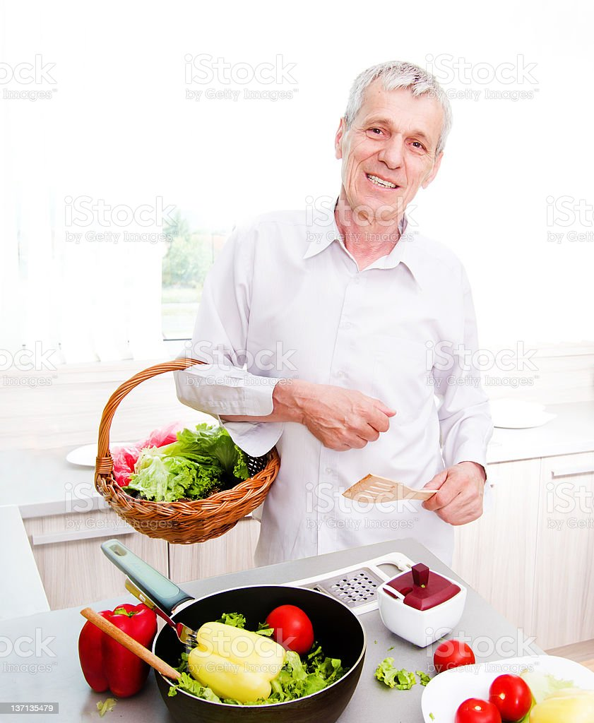 Elderly man preparing vegetable launch in the kitchen royalty-free stock photo