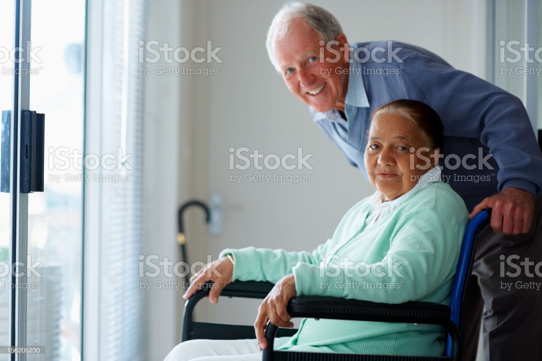 Elderly man pushing her wife on a wheelchair royalty-free stock photo