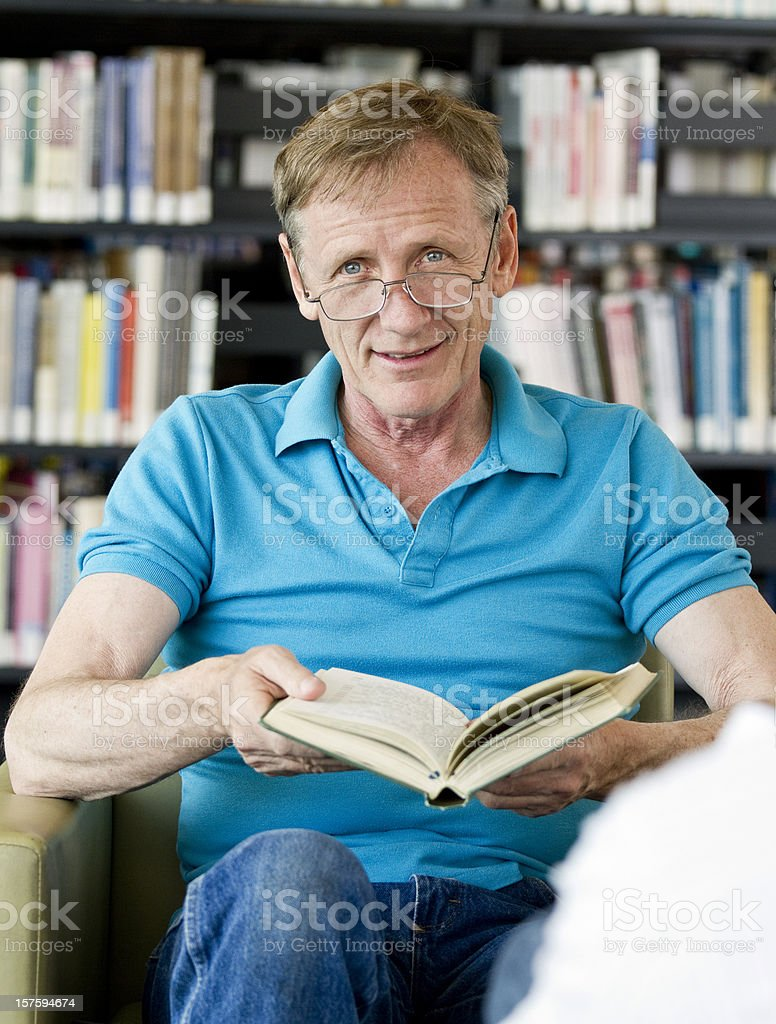 Elderly man reading book at library royalty-free stock photo