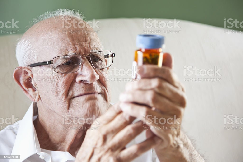 Elderly man reading medicine bottle stock photo