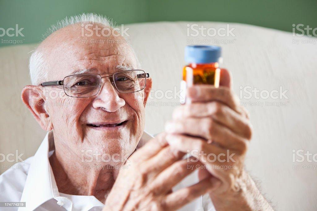 Elderly man reading medicine bottle royalty-free stock photo