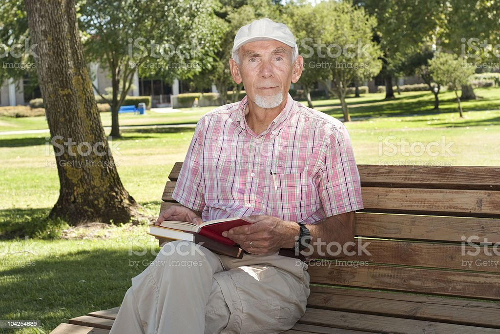 Elderly man reading on bench stock photo