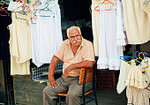 Elderly man sells lingerie and clothes on street market
