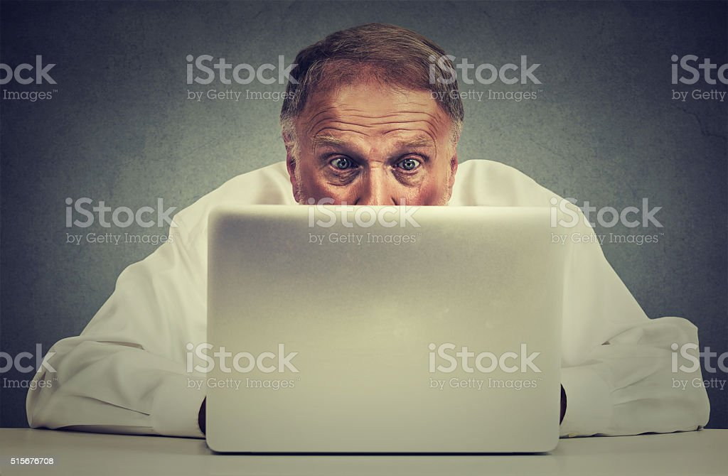 Elderly man sitting at table working on laptop computer stock photo