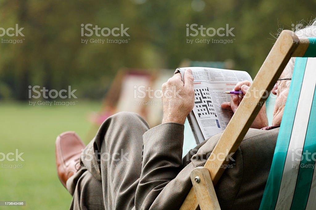 Elderly man sitting in deckchair outside doing crossword stock photo