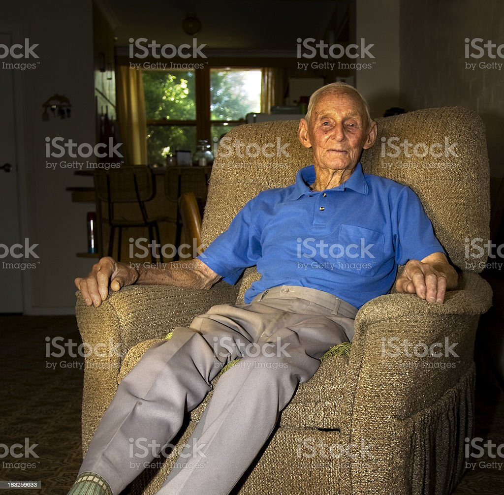Elderly Man sitting in his arm chair stock photo