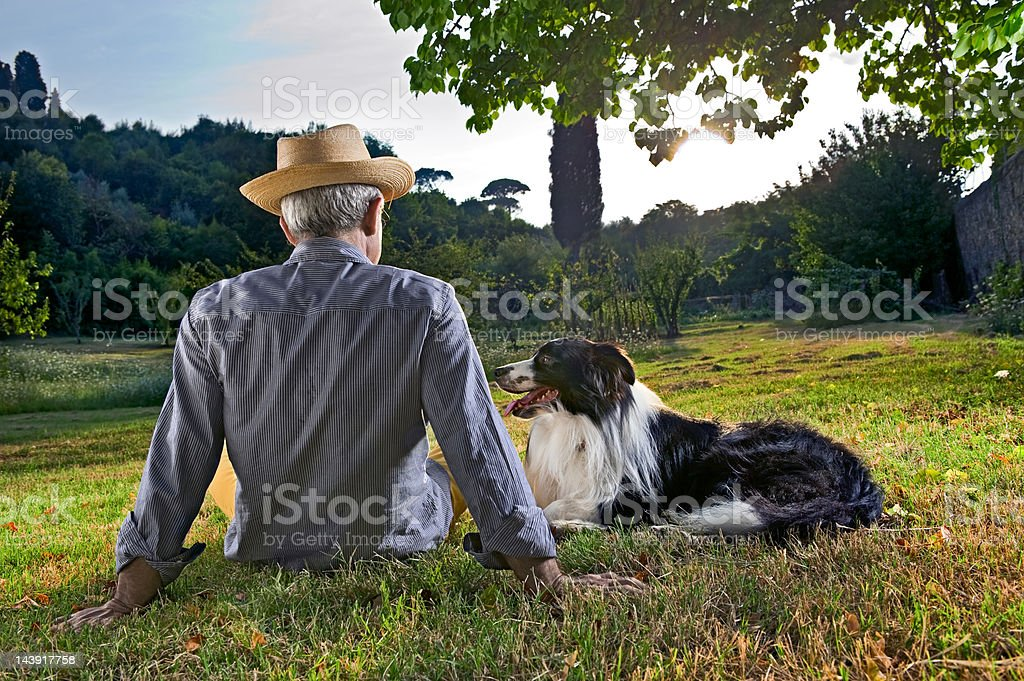 Elderly Man Sitting In Sunset With His Dog.Color Image royalty-free stock photo