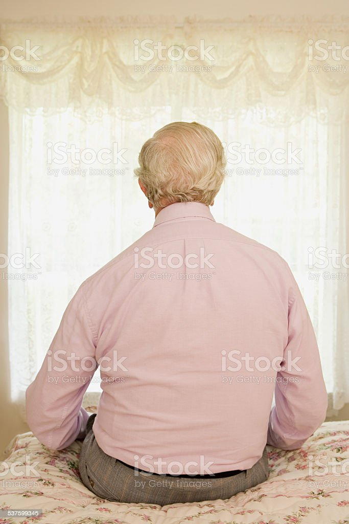 Elderly man sitting on a bed stock photo