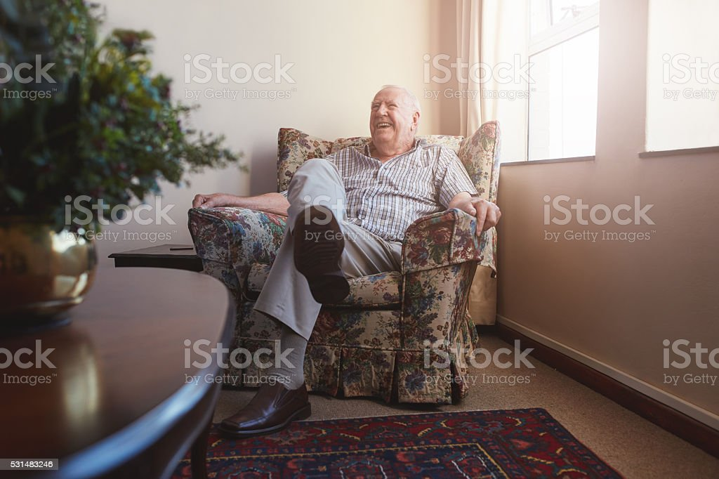 Elderly man sitting on arm chair at old age home stock photo