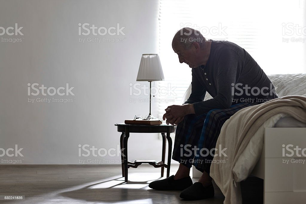 Elderly man sitting on bed looking serious stock photo