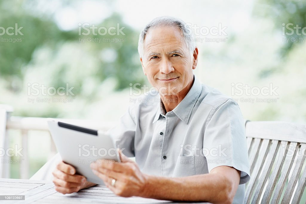Elderly man sitting on bench while holding tablet PC royalty-free stock photo