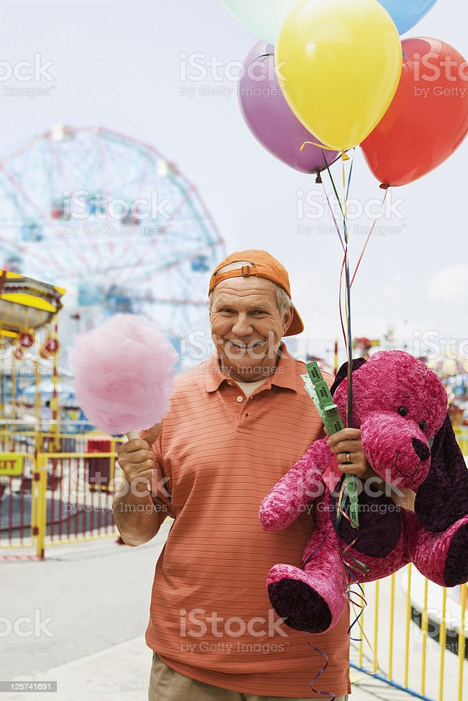 Elderly man smiling and holding cotton candy, baloons and teddy bear stock photo