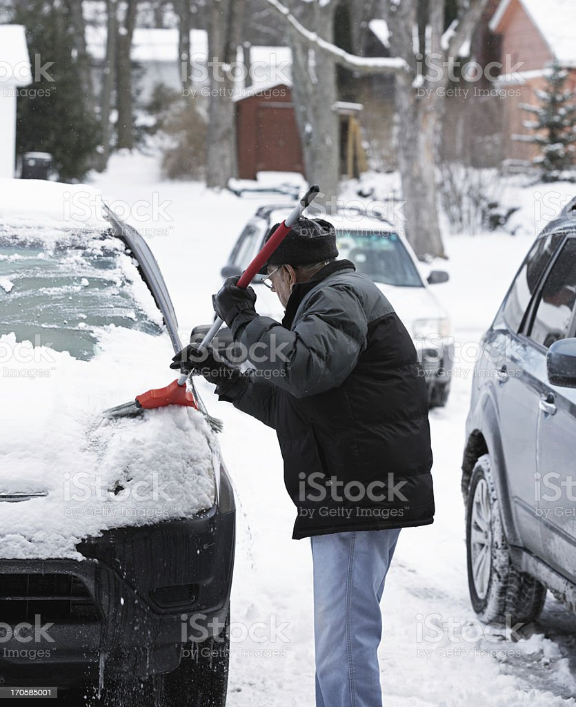 Elderly Man Sweeping Snow From Car Windshield stock photo