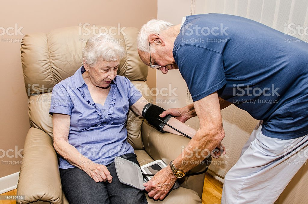 Elderly man taking blood pressure of his wife stock photo